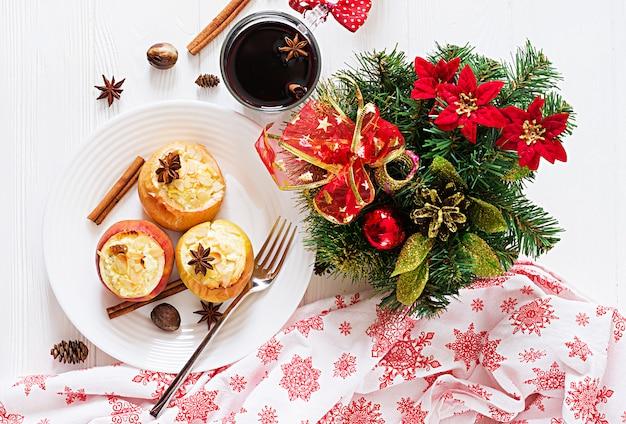 Gevulde gebakken appels met kwark, rozijnen en amandelen voor kerstmis op een witte tafel. xmas eten dessert. Gratis Foto