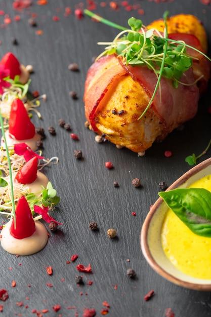 Gevulde kipfilet gewikkeld in spek op een plaat close-up Premium Foto