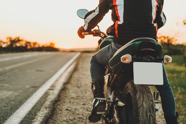 Gewas achteraanzicht van mannelijke ruiter in beschermende laarzen en jas verplaatsen op snelweg van langs de weg op backlit onscherpe achtergrond van lege route Premium Foto