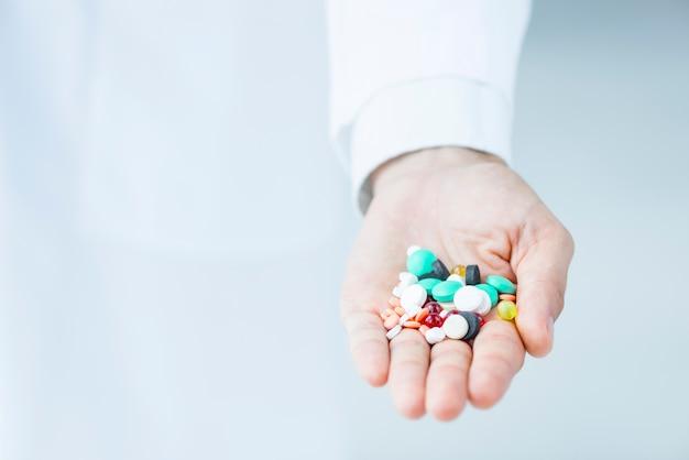 Gewas hand met verschillende pillen Gratis Foto