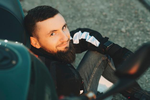Gewas weergave van gelukkige jonge bebaarde man in biker jasje zittend op de weg leunend naar motor camera kijken Premium Foto