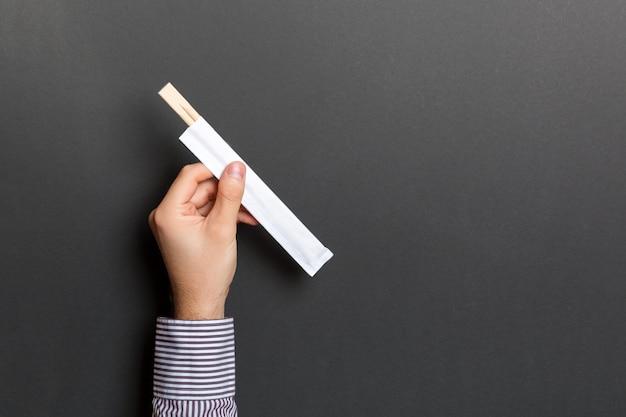 Gewassenbeeld van de mannelijke eetstokjes van de handholding op zwarte achtergrond Premium Foto