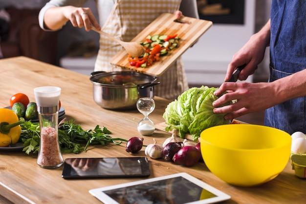 Gewassenpaar dat gezonde salade voorbereidt Gratis Foto