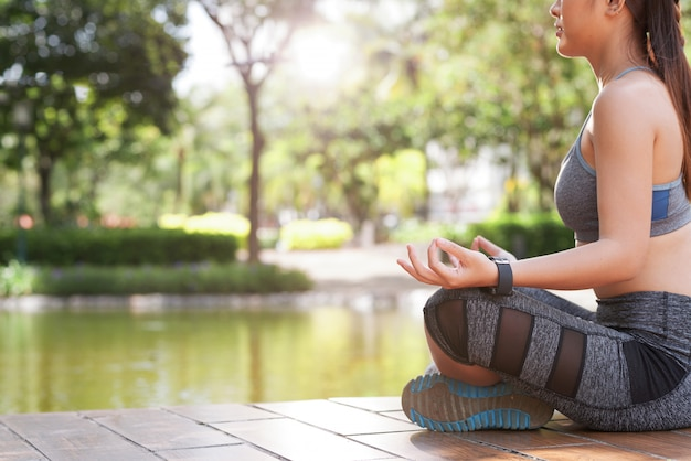 Gewassenvrouw die in groen de zomerpark mediteren Gratis Foto