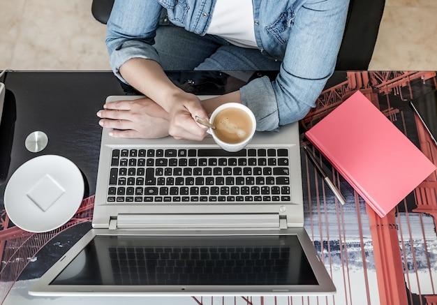 Gewasvrouw die hete drank hebben en laptop met behulp van die op afstand werken Premium Foto