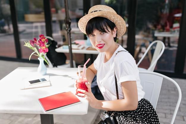 Geweldig blauwogige meisje met donker haar onder strooien hoed rusten in café aan de tafel met laptop, telefoon en bloemen erop Gratis Foto