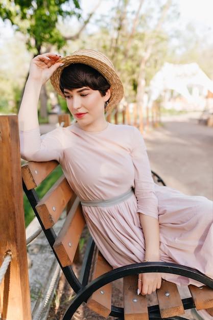 Geweldig brunette meisje comfortabel geregeld op een houten bank en na te denken over iets Gratis Foto