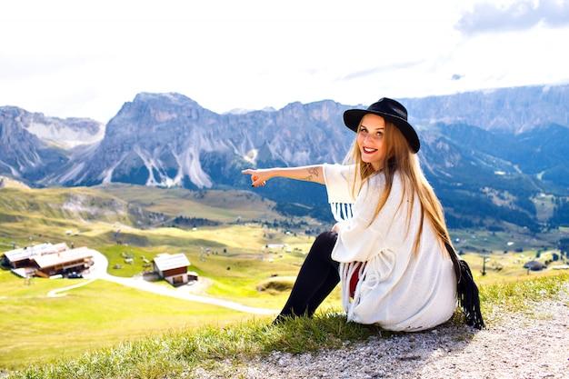 Geweldig buiten portret van boho stijlvolle vrouw poseren in luxeresort met adembenemend uitzicht op de bergen, door haar hand laten zien naar de italiaanse dolomieten. Gratis Foto