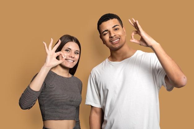 Geweldig huwelijkspaar met okey-symbolen komen overeen met een goede kwaliteit van het product dragen vrijetijdskleding geïsoleerd bruin Premium Foto