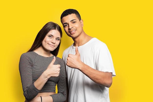 Geweldig huwelijkspaar met okey-symbolen komen overeen met een goede kwaliteit van het product dragen vrijetijdskleding geïsoleerd geel Premium Foto
