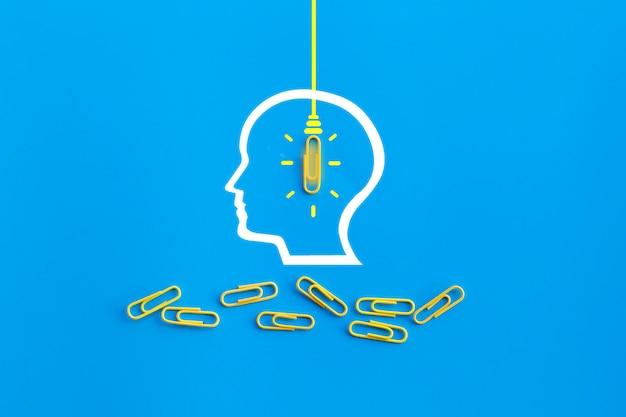 Geweldig ideeënconcept met menselijke hersenen, paperclip, het denken, creativiteit, gloeilamp op blauwe achtergrond, nieuw ideeënconcept Premium Foto