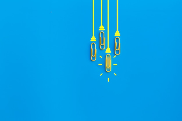 Geweldig ideeënconcept met paperclip, het denken, creativiteit, gloeilamp op blauwe achtergrond, nieuw ideeënconcept. Premium Foto