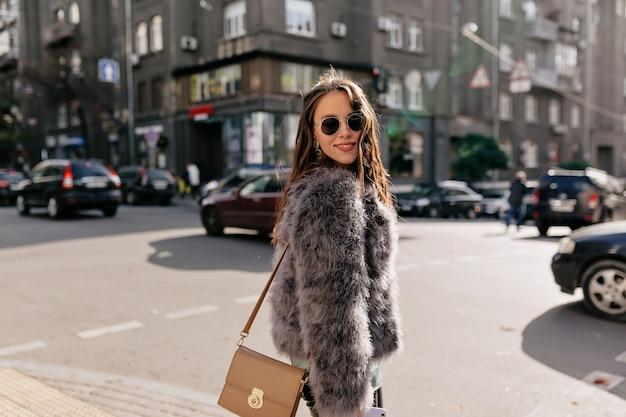 Geweldig meisje met naakt make-up stijlvolle herfst outfit dragen op zonnige stad Gratis Foto