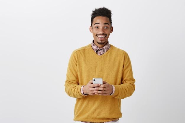 Geweldig nieuws delen met een vriend. portret van een gelukkige opgewonden donkere man in trendy outfit, smartphone vasthoudend, starend met een brede glimlach, op wolk negen van geluk Gratis Foto