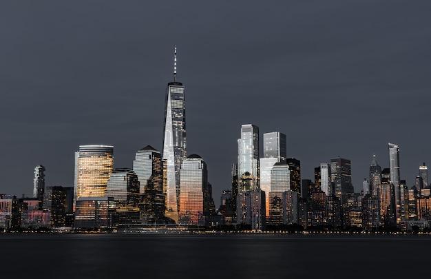 Geweldig schot van de hoge moderne wolkenkrabbers van de skyline van de stad 's nachts Gratis Foto
