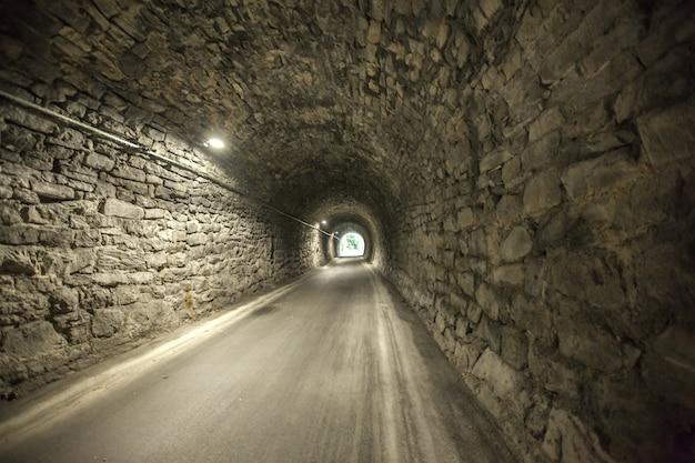 Geweldig schot van de ingang van een oude stenen tunnel vanaf het andere uiteinde van een oude stenen tunnel Gratis Foto