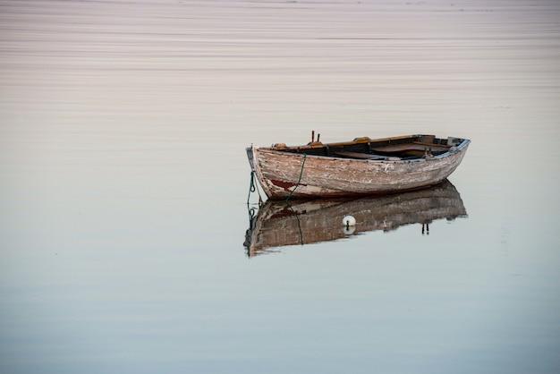 Geweldig shot van een oude houten boot op een reflecterend meer Gratis Foto