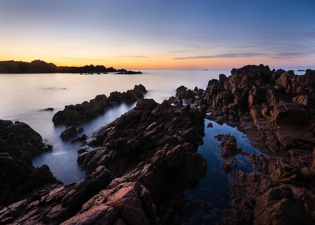 Geweldig shot van een rotsachtig strand bij zonsondergang Gratis Foto