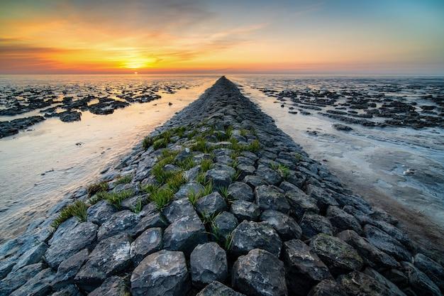 Geweldig shot van een rotsachtig strand op zonsondergang afstand Gratis Foto