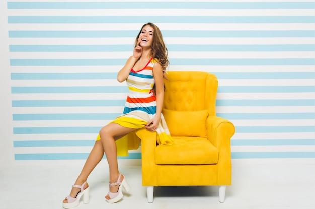 Geweldig vrolijk meisje met lange gebruinde benen zittend op gele fauteuil en haar gezicht met de hand aan te raken. portret van een prachtige jonge dame trendy sandalen en kleurrijke kleding dragen. Gratis Foto