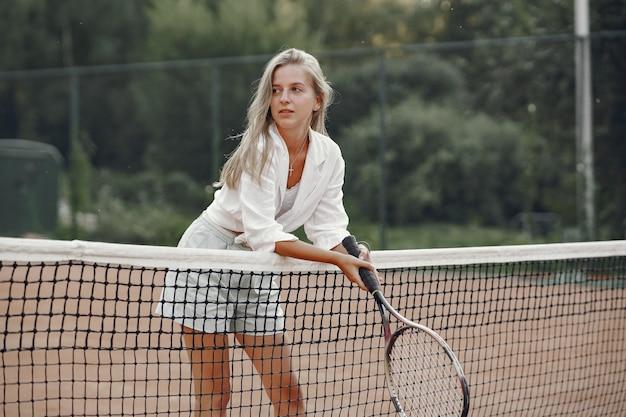 Geweldige dag om te spelen! vrolijke jonge vrouw in t-shirt. vrouw met tennisracket en bal. Gratis Foto