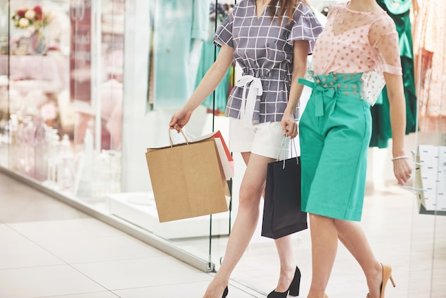 Geweldige dag om te winkelen. twee mooie vrouwen met tassen kijken elkaar met een glimlach tijdens het wandelen in de kledingwinkel Gratis Foto