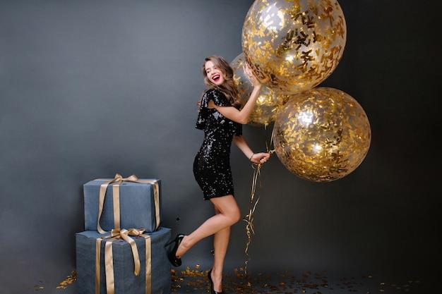 Geweldige modieuze jonge vrouw op hakken, in zwarte luxe jurk met grote ballonnen vol met gouden tinsels. cadeautjes, verjaardagsfeestje, vieren, glimlachen, positiviteit uiten. Gratis Foto