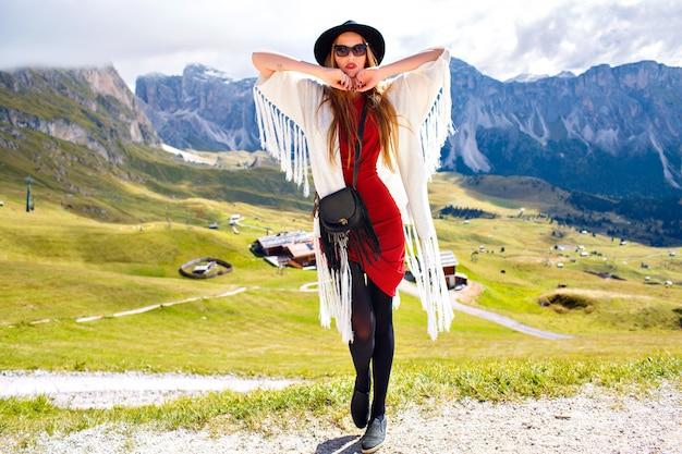 Geweldige outdoor portret van boho stijlvolle vrouw poseren in luxeresort met adembenemend uitzicht op de bergen, vakantie-reiservaring. Gratis Foto