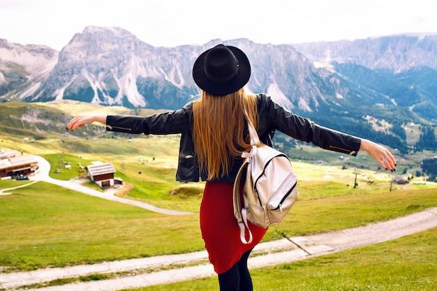 Geweldige reiservaring beeld van mooie stijlvolle vrouw poseren terug en kijken naar adembenemend uitzicht op de bergen, reis in de italiaanse dolomieten. hipster meisje dat van avonturen geniet. Gratis Foto