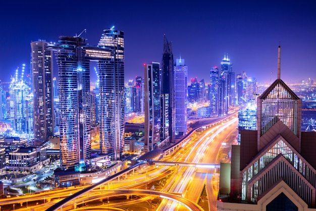 Geweldige skyline stadsgezicht met verlichte wolkenkrabbers. centrum van dubai 's nachts, verenigde arabische emiraten. Premium Foto