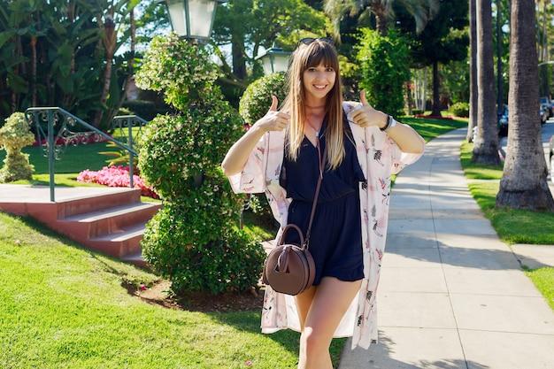 Geweldige stijlvolle vrouw in blauwe playsuit en witte kimono genieten van vakantie. ze lacht en vertoont tekenen. Gratis Foto