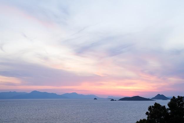 Geweldige strandzonsondergang met eindeloze horizon en ongelooflijke schuimende golven. vulkanische heuvels op de achtergrond. Premium Foto