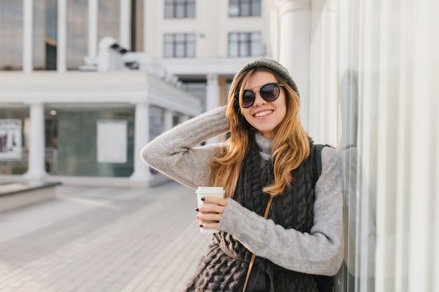 Geweldige vrouw in stijlvolle zonnebril met blonde haren genieten van koffie en poseren buiten met hand omhoog. portret van glimlachende vrouw in hoed en gebreid sweatshirt die zich op stadsstraat in ochtend bevinden. Gratis Foto