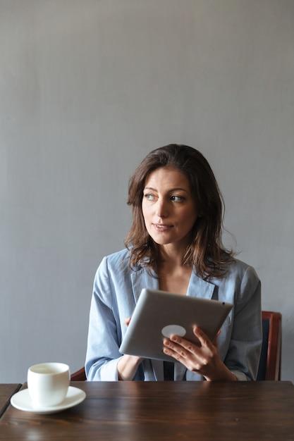 Geweldige vrouw zitten binnenshuis met behulp van tablet-computer. Gratis Foto