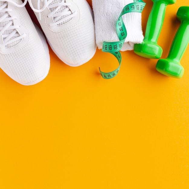 Gewichten en sneakers op diepgele achtergrond met kopie ruimte Gratis Foto