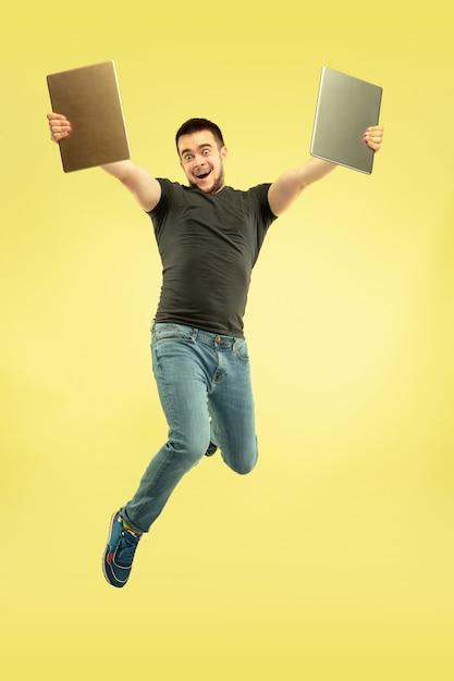 Gewichtloos. volledig lengteportret van gelukkige springende mens met gadgets die op geel worden geïsoleerd. Gratis Foto