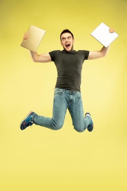 Gewichtloos. volledig lengteportret van gelukkige springende mens met gadgets die op gele achtergrond worden geïsoleerd. moderne technologie, concept van vrijheid van keuzes, concept van emoties. tablet gebruiken voor selfie of vlog tijdens de vlucht. Gratis Foto