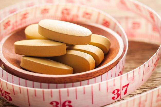 Gewichtsverlies vitamine en meetkabel op houten textuur, gezonde voeding concept Premium Foto