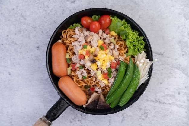 Gewokte noedels met varkensgehakt, edamame, tomaten en champignons in een pan. Gratis Foto