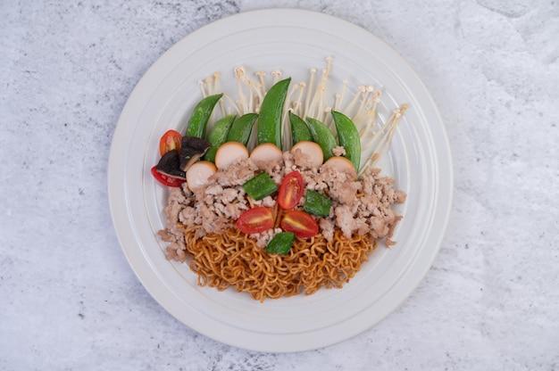 Gewokte noedels met varkensgehakt, edamame, tomaten en champignons in een witte plaat. Gratis Foto