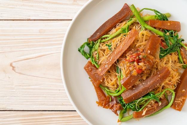 Gewokte rijstvermicelli en watermimosa met gepekelde inktvis Premium Foto