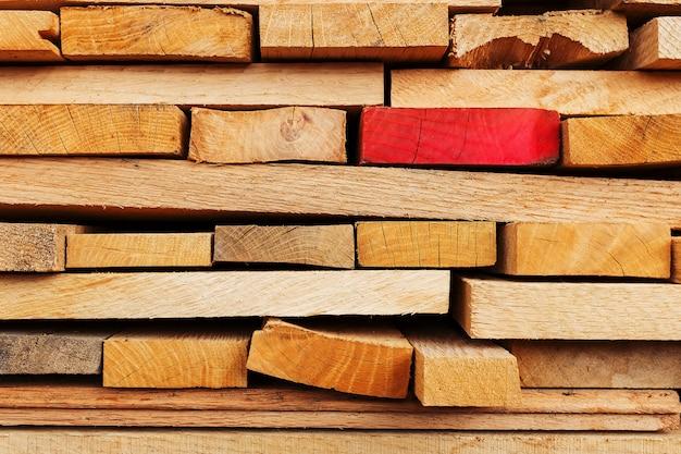 Gezaagde en gevouwen planken met de nadruk op één rood bord, constructieplanken, timmerhoutachtergrond. Premium Foto