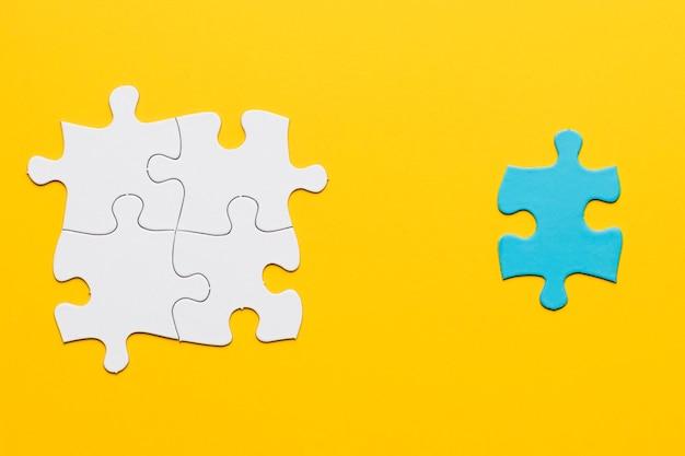 Gezamenlijke witte puzzel met een blauw stuk op geel oppervlak Gratis Foto