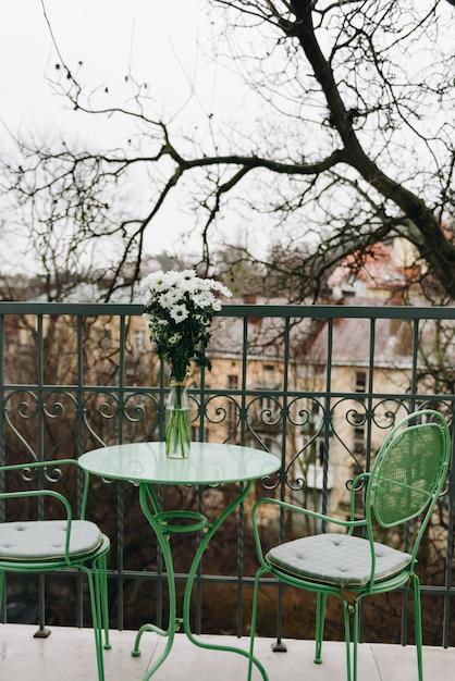 Gezellig balkon met groene tafel en stoelen Premium Foto