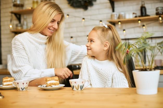 Gezellig beeld van gelukkige jonge moeder met lang blond haar poseren in de keuken met haar schattige dochter, zittend aan tafel, thee hebben en eten taart, elkaar aankijken en glimlachen, praten Gratis Foto