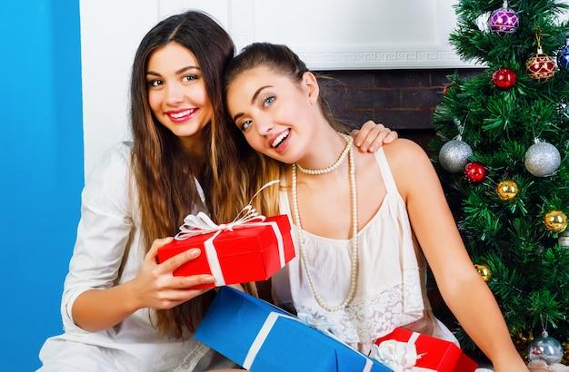 Gezellig helder wit vakantieportret van twee beste vrienden, mooie zussen, zittend bij de open haard en een versierde kerstboom en met cadeautjes van hun familie. positieve emoties en stemming. Gratis Foto