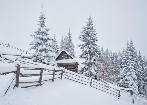 Gezellige houten hut hoog in de besneeuwde bergen. Premium Foto