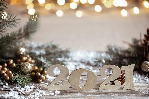 Gezellige kerst achtergrond met decoratieve houten 2021 nummers op onscherpe achtergrond met verlichting. Gratis Foto