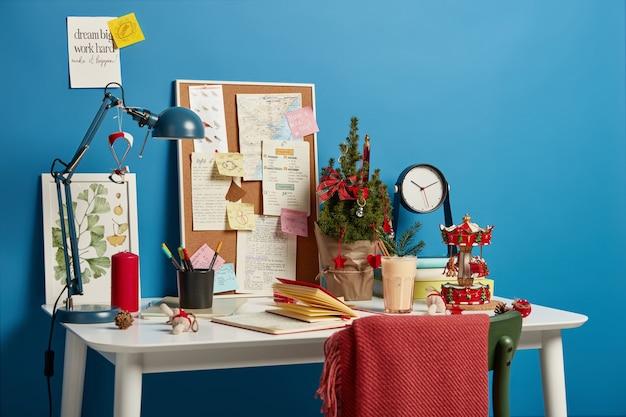 Gezellige werkruimte met versierde kerstboom, traditioneel winterdrankje, bord met memo's om nooit te vergeten, bureaulamp voor een goede verlichting. Gratis Foto