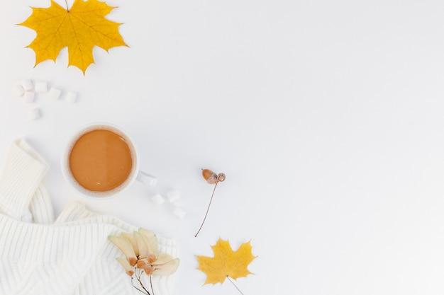 Gezellige witte warme trui en koffiekopje herfststemming en witte achtergrond Premium Foto